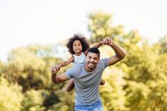 Retrato del padre joven que lleva a su hija en el suyo detrás foto de archivo libre de regalías