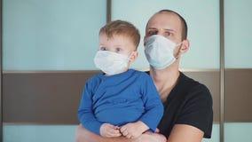 Retrato del padre que detiene el pequeño niño lindo del bebé del niño que lleva la máscara médica protectora, el papá y al hijo q almacen de video