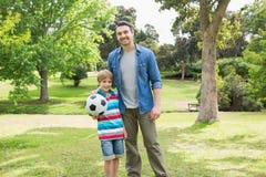 Retrato del padre y del hijo con la bola en el parque foto de archivo