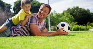 Retrato del padre y del hijo felices con el fútbol que miente en parque almacen de metraje de vídeo
