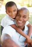 Retrato del padre y del hijo felices en parque Imagen de archivo libre de regalías