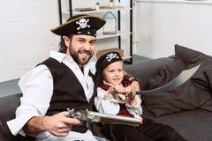 retrato del padre y del hijo emocionales en los disfraces de Halloween de los piratas que se sientan en el sofá foto de archivo