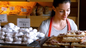 Retrato del panadero de sexo femenino que sostiene la comida dulce en bandeja almacen de metraje de vídeo