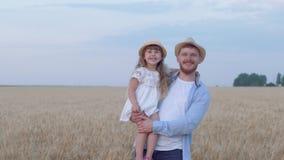 Retrato del papá feliz con la muchacha del niño, estancias del hombre joven con la hija sonriente alegre en sus manos que miran u metrajes