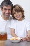 Retrato del papá y del hijo que desayunan junto Imagen de archivo libre de regalías