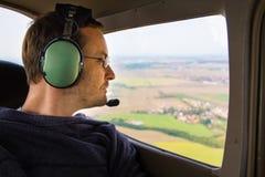 Retrato del pasajero adulto joven que sienta en privado el avión de aire y que mira hacia fuera la ventana Imagenes de archivo