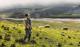 Retrato del pastor With Sheep On The Field en montañas, Witb Fotos de archivo libres de regalías