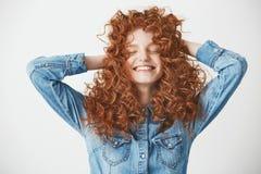 Retrato del pelo conmovedor de la muchacha hermosa astuta que sonríe con los ojos cerrados sobre el baackground blanco Fotos de archivo libres de regalías