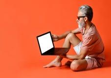 Retrato del pensionista de moda que disfruta del uso del nuevo ordenador portátil fotografía de archivo libre de regalías