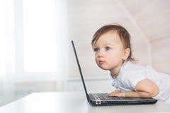 Retrato del pequeño bebé que mira un lado con un ordenador portátil imagenes de archivo