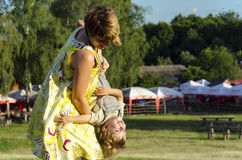 Retrato del pequeño de la mamá el besarse y de la sacudida hijo feliz al aire libre en jardín verde del verano Imagen de archivo