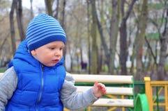 Retrato del pequeño muchacho agradable en un casquillo en la primavera temprana imagen de archivo