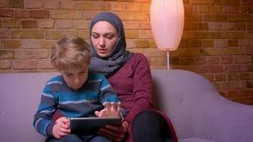 Retrato del pequeño muchacho concentrado que se sienta con su madre musulmán en el hijab que juega al juego en la tableta en casa metrajes
