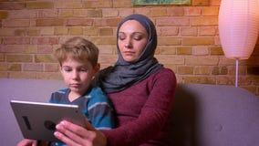 Retrato del pequeño muchacho concentrado y de su madre musulmán en película de observación del hijab en la tableta y la discusión almacen de metraje de vídeo