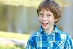 Retrato del pequeño muchacho feliz sobre el fondo soleado de la naturaleza, risa imagen de archivo libre de regalías