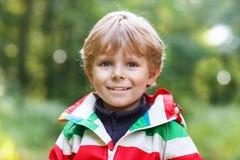 Retrato del pequeño muchacho preescolar rubio en la prenda impermeable colorida r Fotos de archivo libres de regalías