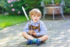 Retrato del pequeño muchacho rubio del niño con la espada del juguete Fotografía de archivo libre de regalías