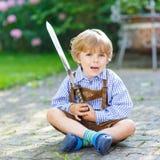 Retrato del pequeño muchacho rubio del niño con la espada del juguete Fotos de archivo