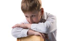 Retrato del pequeño muchacho rubio en la camisa blanca que se inclina en la silla Foto de archivo