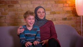 Retrato del pequeño muchacho y de su madre musulmán en el hijab que abraza y que ve la TV junto el sentarse en el sofá en casa almacen de video