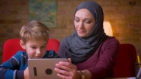 Retrato del pequeño muchacho y su de la madre musulmán en hijab que miran en la tableta junto y la discusión almacen de metraje de vídeo
