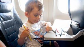 Retrato del pequeño niño pequeño con los lápices coloridos en aeroplano imagen de archivo libre de regalías