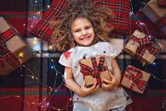 Retrato del pequeño niño lindo sonriente en los pijamas de la Navidad del día de fiesta que sostienen la caja de regalo Visión su fotografía de archivo libre de regalías