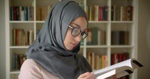 Retrato del perfil del estudiante musulm?n en libro de lectura del hijab y de los vidrios atento en la biblioteca almacen de video