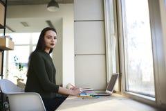 Retrato del periodista joven hermoso que trabaja en la escritura del nuevo artículo en espacio coworking fotos de archivo