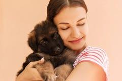 Retrato del perrito del pastor alemán que presenta en las manos del ` s de la mujer foto de archivo libre de regalías