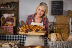 Retrato del personal femenino sonriente que sostiene la bandeja de comida dulce en el contador del pan foto de archivo