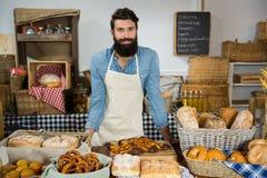 Retrato del personal masculino que se coloca en el contador de la panadería foto de archivo libre de regalías