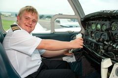 Retrato del piloto joven con Síndrome de Down en cabina. Foto de archivo libre de regalías