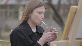Retrato del pintor de la chica joven que se sienta delante del caballete de madera que dibuja una imagen y fumar r metrajes