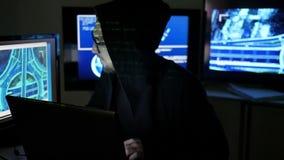 Retrato del pirata informático, espionaje de Internet, hurto de identidad, pirata informático que usa el ordenador portátil, orde almacen de video