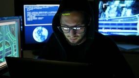 Retrato del pirata informático, sistema que se agrieta criminal masculino, pirata informático que usa el ordenador portátil, orde metrajes