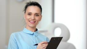 Retrato del placer femenino joven sonriente del doctor que trabaja en el primer medio de la clínica moderna almacen de video