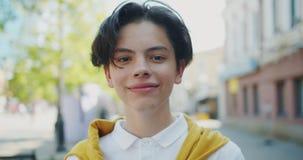 Retrato del primer del adolescente alegre que sonríe mirando la cámara en día ventoso metrajes