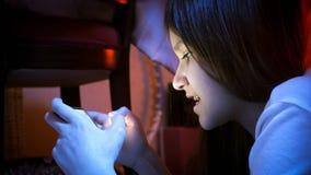 Retrato del primer del adolescente lindo que usa smartphone en la noche Imagen de archivo