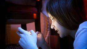 Retrato del primer del adolescente que hojea en ternet en el teléfono móvil en la noche Imagen de archivo libre de regalías