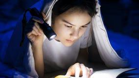 Retrato del primer del adolescente que miente debajo de la manta y del libro de lectura Fotos de archivo