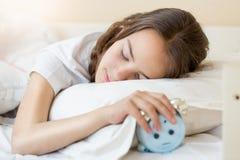 Retrato del primer del adolescente que miente en cama y que sostiene el despertador disponible Imagen de archivo