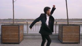 Retrato del primer del baile afroamericano atractivo joven y de hacer del hombre de negocios los movimientos de la barajadura que metrajes