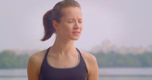 Retrato del primer del basculador femenino deportivo bonito joven que mira adelante con el cielo azul en el aire libre del fondo metrajes