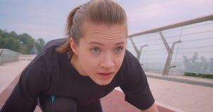 Retrato del primer del basculador femenino deportivo resuelto joven en una camiseta negra que se sienta en una posición de comien almacen de video