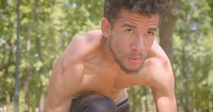 Retrato del primer del basculador masculino afroamericano descamisado joven que se prepara para correr en el parque que es determ almacen de metraje de vídeo