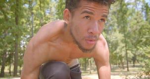 Retrato del primer del basculador masculino afroamericano descamisado joven que se prepara para correr en el parque que es motiva metrajes