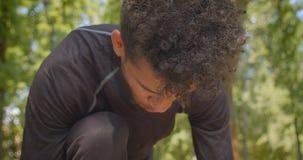 Retrato del primer del basculador masculino afroamericano fuerte joven que se prepara para correr en el parque al aire libre metrajes
