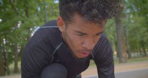Retrato del primer del basculador masculino afroamericano fuerte joven que se prepara para correr en el parque que es determinado almacen de video