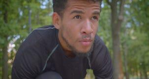 Retrato del primer del basculador masculino afroamericano fuerte joven que se prepara para correr en el parque que es motivado al almacen de metraje de vídeo